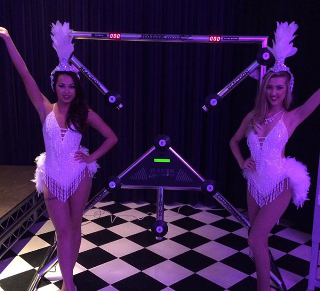 Batak with showgirls on an exhibition stand at Excel